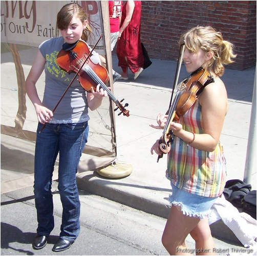 Girls busk with violins at Lilac