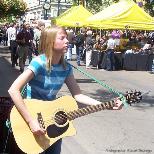 Young guitarist busking on the Ave